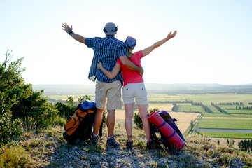 young couple with backpack on adventure mountain trek admiring a beautiful sunset landscape