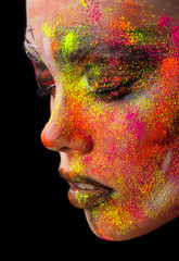 Beauty fashion portrait of a girl close-up. bright creative make-up. Face model sprinkled colored powder