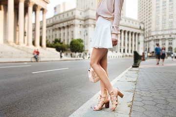 Beautiful long female legs. Beautiful woman standing on city street wearing fashionable summer outfit. Girl on high heels, white skirt, pink t-shirt holding clutch bag. Wall mural