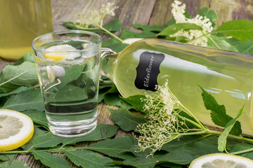 Glass of water with Elderflower Syrup and Lemon with lying Bottl