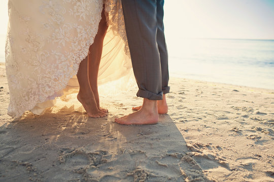 Bride and groom are standing at the beach