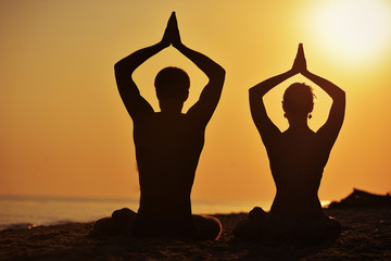 man and woman in a lotus position silhouette