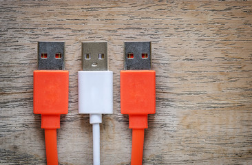 Orange and white USB cable Plug on wooden background.