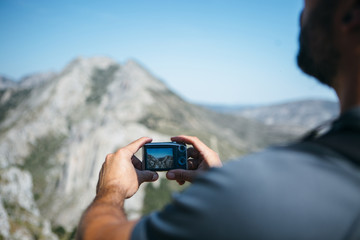 Traveler taking photograph of mountains