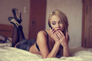 Sexy hot blonde woman calling on bed by phone