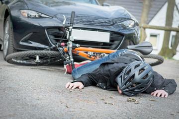 radfahrer liegt verletzt vor einem auto