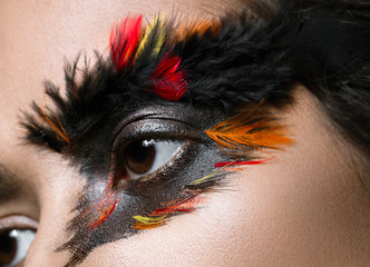 Beautiful girl in image of Phoenix bird with creative makeup. beauty face. Close up
