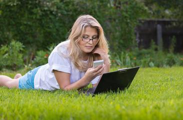 Красивая женщина  на траве в саду с ноутбуком