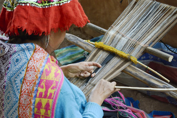 Peruvian woman in traditional clothing weaving cloth on a hand loom