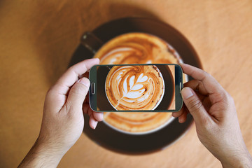 Hand holding smartphone taking photo of coffee. from above,topvi