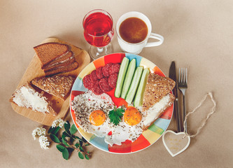 Delicious Breakfast from Eggs,Bread with Butter,Sausage on the Colorfull Plate.Coffee,Red Juice  with White Flowers.Brown Background.
