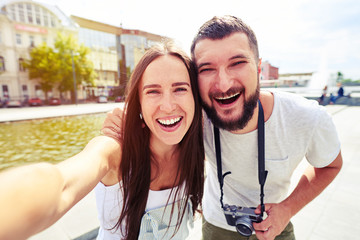 Young couple smiling sincerely while making selfie