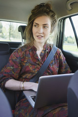 Thoughtful young woman using laptop in car