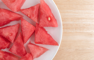 Small sections of watermelon on a white plate atop a wood table.