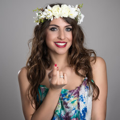 Portrait of young fairy girl with flower wreath smiling with inviting finger gesture over gray studio background