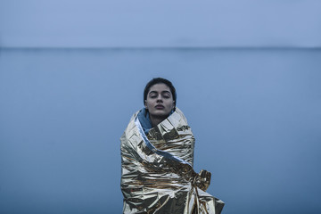 Teenage girl with eyes closed wrapped in golden plastic against lake