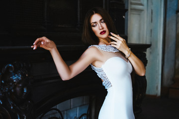 the effect of film photography. Beautiful sexy woman with long dark hair. Dressed in a white long dress with a train at the floor. Posing in an abandoned old castle on a background of fire.
