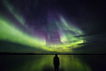 Silhouette of person watching Aurora borealis, Finland