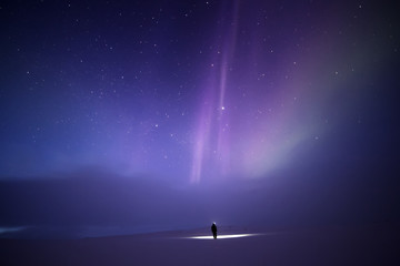 Person bathed in light from Aurora borealis, Finland