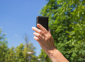 The phone in hand of old woman on the blue sky background