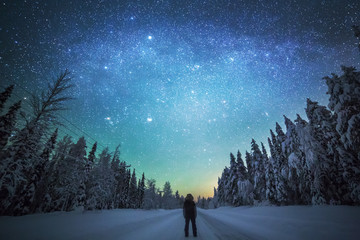 Rear view of man standing on snowy landscape against starry sky