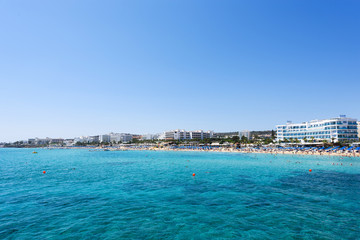 Photo of sea and fig tree bay beach in protaras, cyprus island with swimming people and hotels.