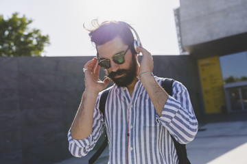 Bearded young man with sunglasses listening music with headphones