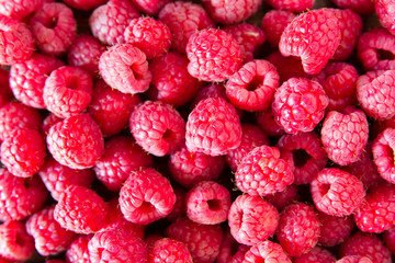 Ripe sweet juicy raspberries on wooden table. Close up, top view
