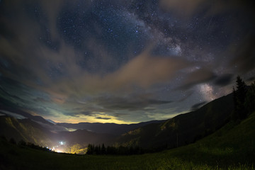 Milky way over a mountain valley and village