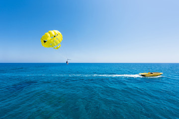 Photo of sea in protaras, cyprus island with parasailing and a boat.