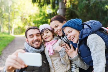 family with backpacks taking selfie by smartphone