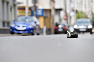 Shoe on the street with cars in background after accident