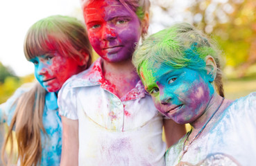 cute european child girls celebrate Indian holi festival with co