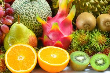 Closeup orange slice juice with various tropical fruits, Closeup tropical fruits for healthy
