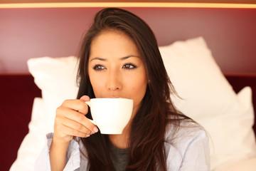 Frau trinkt morgens im Bett ein Kaffee
