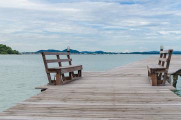 Bench on wooden bridge to the sea