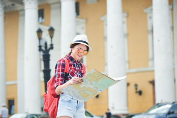 The girl tourist with hat and sunglasses holding a map and looking at her against the building with columns