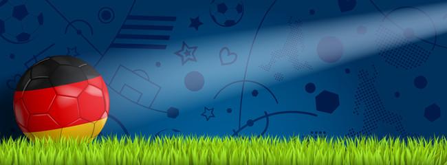 Deutschland Ball vor blauem Hintergrund auf Rasen