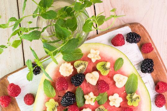 Fruit watermelon pizza with fresh berries, banana, kiwi and mint