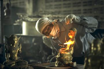 Man welding a traditional buddah sculpture, Thailand