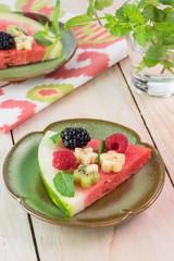 Piece of fruit watermelon pizza with fresh berries, banana, kiwi