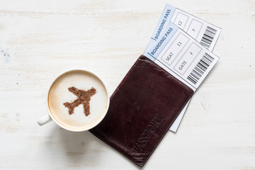 Aircraft symbol made of cinnamon in cup of cuppuccino, boarding passes and passports. Traveling concept