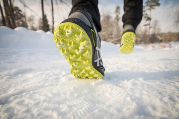 Running shoes close up. Legs runner close up. Trail running on a snow-covered winter trail. Motivation concept