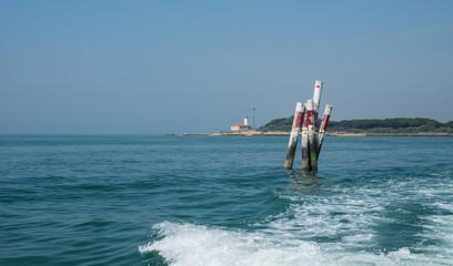 Bootswellen am Mittelmeer mit Begrenzung und Leuchtturm im Hintergrund