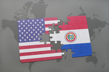 puzzle with the national flag of united states of america and paraguay on a world map background
