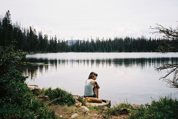 Woman sitting by lake, High Uintas Wilderness area, Utah, America, USA