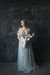 Young beautiful bride in wedding dress posing in studio