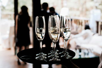 waiter brings full glasses of champagne on a tray
