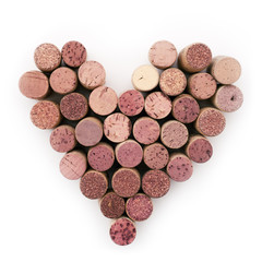 Background of various colored used wine corks in heart's shape close up. Top view. Isolated on white.