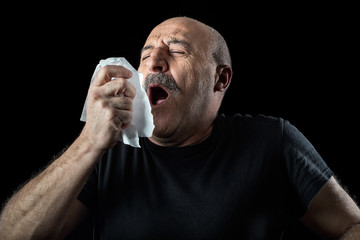 Middle-aged man with flu sneezing into a handkerchief